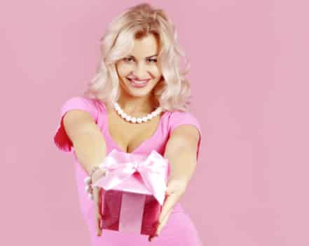 Portrait of blond beautiful girl giving gift on pink background
